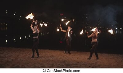 Young fireshow artists juggling staves outdoor - Amazing...