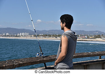 Young fisherman looking over the ocean at a tropical resort