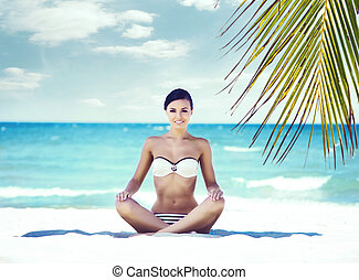 Young, fit and beautiful girl meditating on a summer beach....