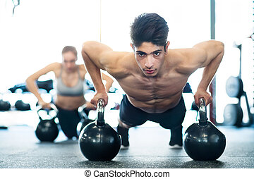 Young fit couple in gym doing push ups on kettlebells -...