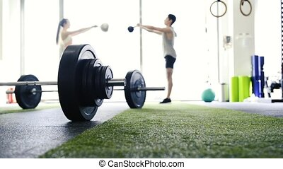 Young fit couple in gym exercising doing kettlebell swings....