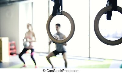 Young fit couple in gym exercising with kettlebells.