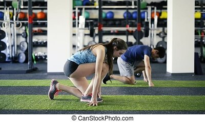 Young fit couple in gym fast running. Young man and woman...