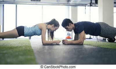 Young fit couple in gym in plank position exercising core...
