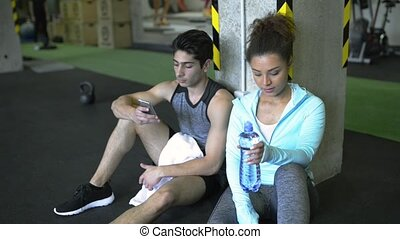 Young fit couple in gym resting, drinking water. - Beautiful...