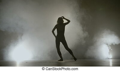 Young fit girl dancing on a smoke background while recording...