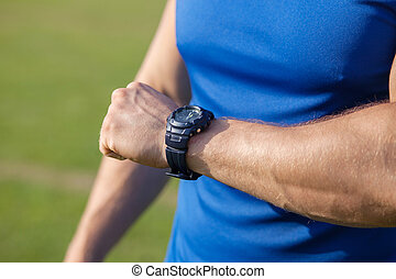 Young fit healthy sportsman is checking time