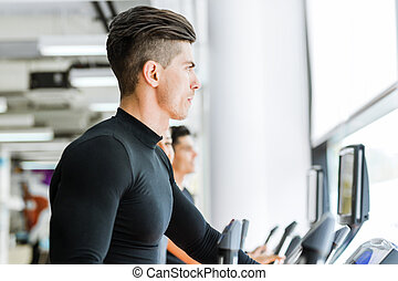 Young fit male jogging in a gym