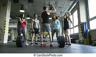 Young fit man in crossfit gym giving high five to his friends.