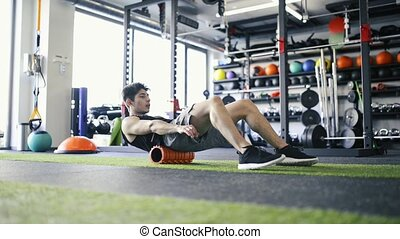 Young fit man in gym doing exercise with foam roller. -...
