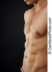 Young fit man is showing his perfect body