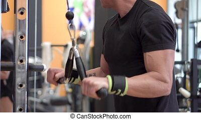Young fit muscular man close up doing triceps pull down rope...