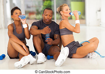 young fit people after exercise drinking water