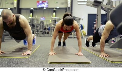 Young fit people in crossfit gym doing push ups.