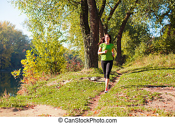 Young fit sport model running through the forest