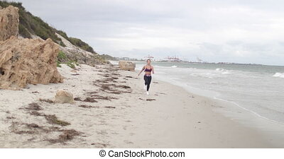 Young fit sports woman jogging on the beach. 4k slow motion stabilizer shot.