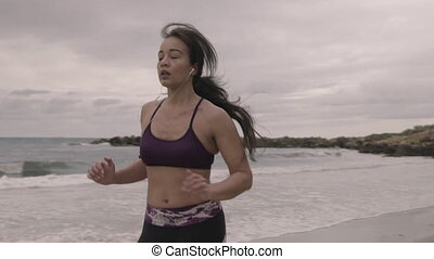 Young fit sports woman jogging on the beach. Super slow motion stabilizer shots.