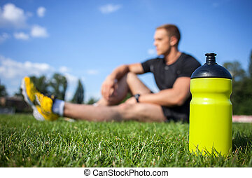 Young fit sportsman is relaxing after training