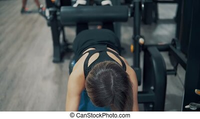 woman doing exercises for legs and buttocks muscles in gym -...