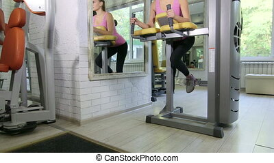 Young fit woman doing hamstrings exercise on leg curl machine in fitness club