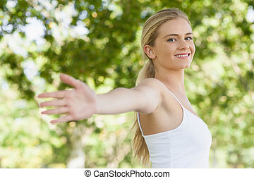 Young fit woman doing yoga in a park spreading her arms...