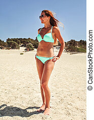 Young fit woman in green blue bikini standing on the beach, wind in her hair.
