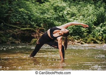 Young fit woman practicing yoga, standing in river, wearing black leggings and top