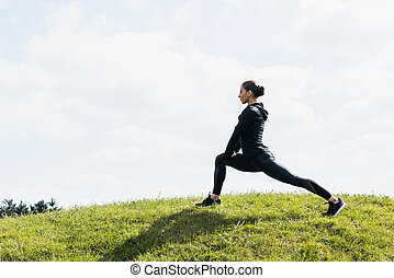fit woman stretching legs