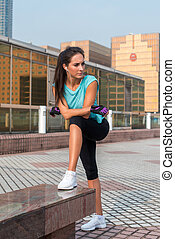 Young fit woman taking a break after exercising or running. Fitness girl standing and resting outdoors on city street.