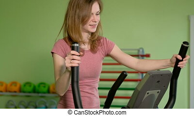 Young fit woman using an elliptic trainer in a fitness center, listening a music with headphones and smiling. Portrait of fitness girl in the gym near a window,. 4k