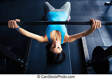 Young fit woman working out with barbell on bench in the...