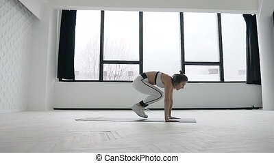 Young fitness blonde woman exercises in gym near big windows during morning sport, training workout. She dressed in white sportswear