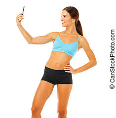 Young fitness brunette woman in blue top and black shorts posing isolated on white background