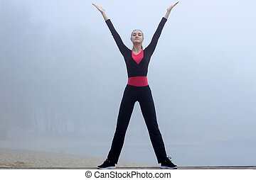 Young fitness girl does yoga exercises during training workout outdoor