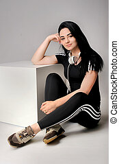 Young fitness girl with cup listening to music on cubes