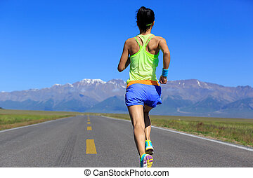 Young fitness healthy lifestyle woman runner running on road with snow capped mountains in the distance