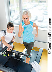 Young fitness instructor woman running at gym