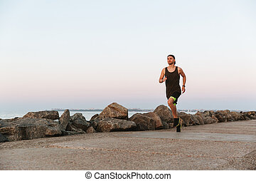 Young fitness mann running outdoors at the beach
