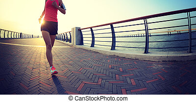 Young fitness sporty woman runner running at sunrise seaside