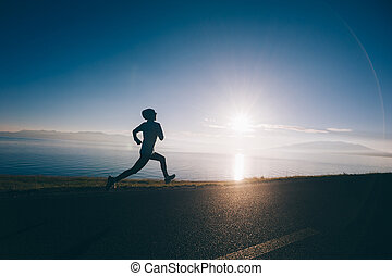 Young fitness sporty woman running on country road