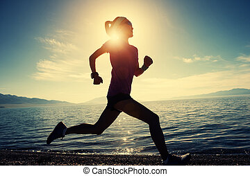 Young fitness sporty woman running on rocky seaside
