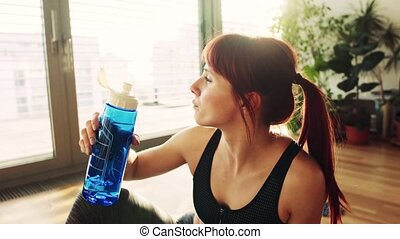 Young fitness woman at home, drinking water from the bottle....