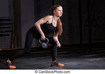 Young fitness woman doing crossfit workout with kettlebell on dark background.