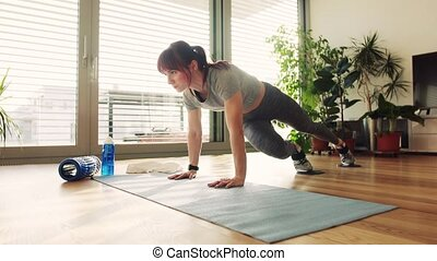 Young fitness woman doing exercise at home.