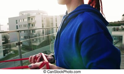 Young fitness woman doing exercise on a balcony at home. -...
