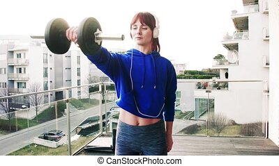 Young fitness woman doing exercise on a balcony at home.