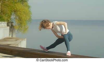 young fitness woman doing exercises on the gym in an outdoor...