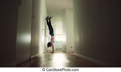 Young fitness woman doing handstand at home. - Beautiful...