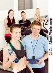 Young fitness woman doing spinning with instructor