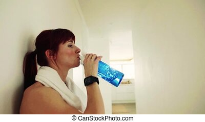 Young fitness woman drinking water at home.
